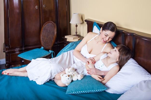 Mama i młoda dziewczyna rano leżą w łóżku, przytulają się, uśmiechają i patrzą na siebie. zdjęcia studyjne