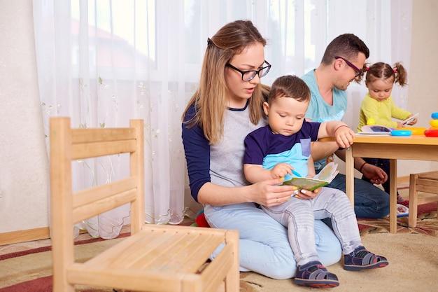 Mama i ojciec czytają książkę z dziećmi w pokoju