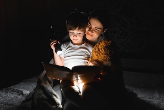 Mama i syn czytają książkę z latarką pod kocem