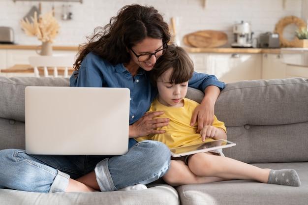 Mama i syn dziecka używają tabletu siedzą na kanapie uśmiechnięta matka pomagają dziecku w lekcjach lub grach e-learningowych