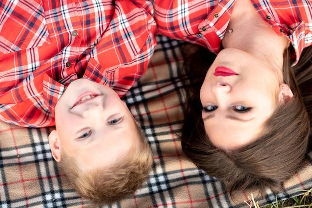 Mama i syn leżą na kocu w kratę. w dowolnym celu.