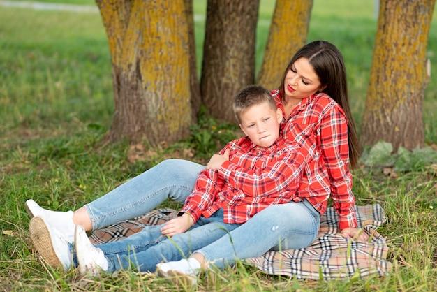 Mama i syn leżą na narzucie, syn marszczy brwi, ściąga usta i patrzy w bok