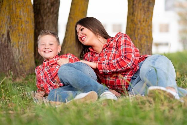 Mama i syn, leżąc na boku na narzucie, śmieją się wesoło. w dowolnym celu.