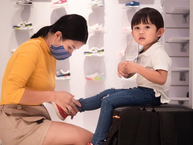 Mama i syn robią zakupy w sklepie z butami i noszą maskę.