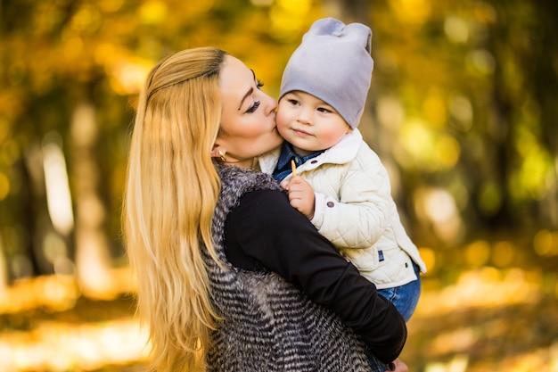 Mama i syn są w jesiennym parku, syn uwielbia patrzeć na matkę, kobieta trzyma go za ręce