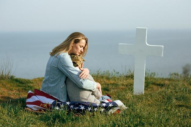 Mama i syn siedzą na grobie żołnierza. mama przyprowadziła syna do grobu ojca w dniu pamięci 27 maja