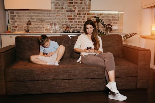 Mama i syn słuchają telefonów komórkowych na sofie w mieszkaniu