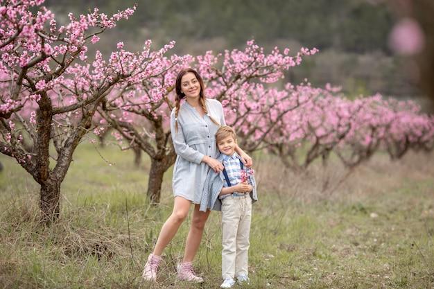Mama i syn spacerują razem i bawią się na podwórku w ogrodzie