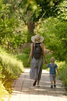 Mama i syn spacerujący po drodze w parku.
