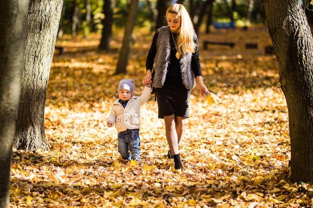 Mama i syn spacerujący po jesiennym parku