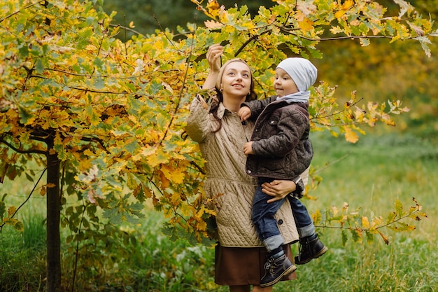 Mama i syn, spacery i zabawa w jesiennym parku.