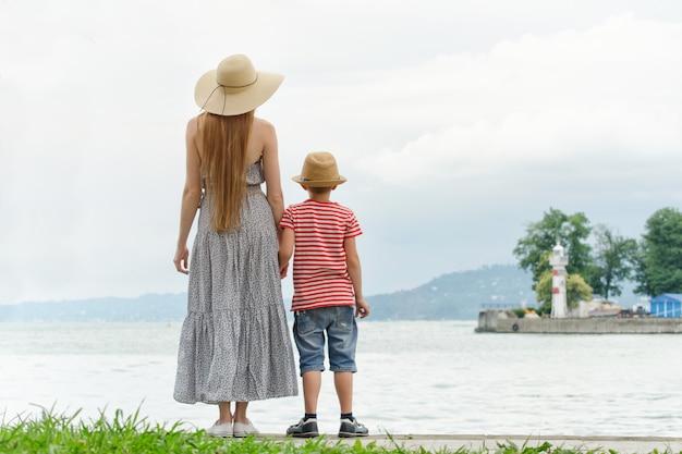 Mama i syn stojący na molo nad morzem, latarnią morską i górami w oddali. widok z tyłu