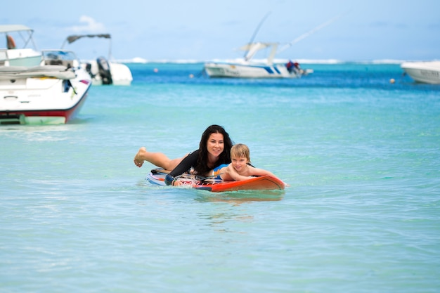 Mama i syn surfują po oceanie na tablicy