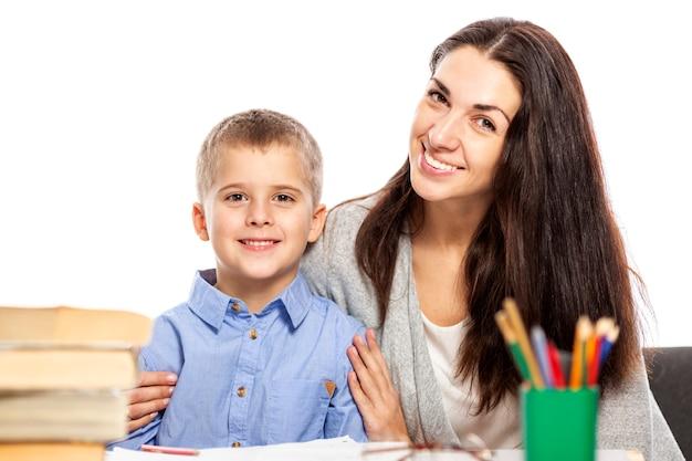 Mama i syn uśmiechają się i przytulają podczas odrabiania lekcji. miłość i czułość białe tło.