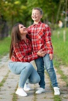 Mama i syn uśmiechają się radośnie na spacerze po parku. w dowolnym celu.