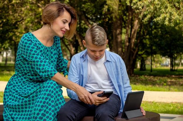 Mama i syn używa pastylkę i smartphone podczas gdy siedzący na naturze