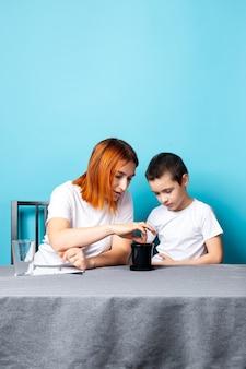 Mama i syn włożyli ziemię do czarnego garnka, aby posadzić nasiona i wyhodować na stole roślinę domową