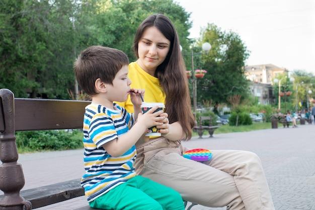 Mama i synek piją kakao w parku w mieście.