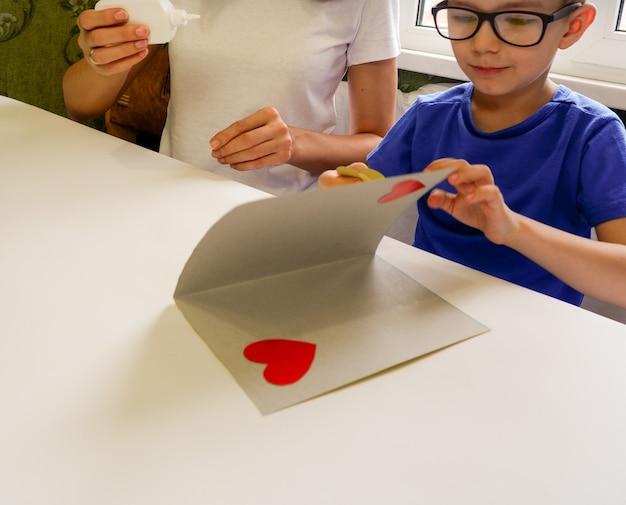 Mama i szczęśliwy syn szczęśliwi robią kartkę na dzień matki, siedząc razem przy stole z papierem i