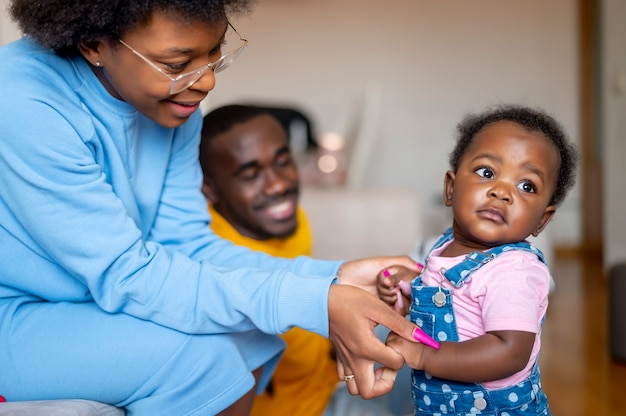 Mama i tata bawią się na sofie ze swoją 9-miesięczną córeczką