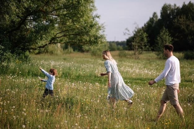 Mama i tata biegną za dzieckiem przez pole, chłopiec bawi się i ucieka od nich. zdjęcie koncepcji przyjęcia