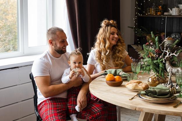 Mama i tata mają śniadanie ze swoim małym dzieckiem w tej samej piżamie
