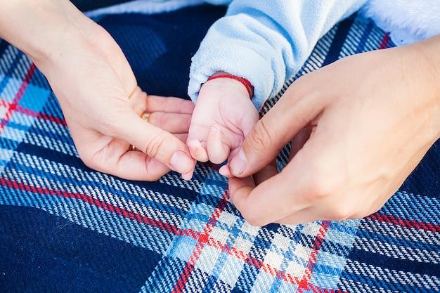 Mama i tata trzymają dłoń swojego małego dziecka