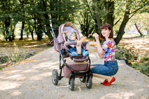 Mama karmi córeczkę łyżeczką. matka daje jedzenie dziesięciomiesięcznemu dziecku chodząc z wózkiem w parku. jedzenie dla dzieci.