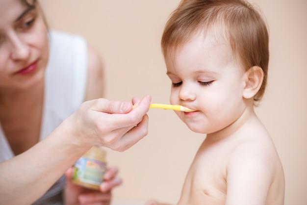 Mama karmi dziecko przecierem owocowym