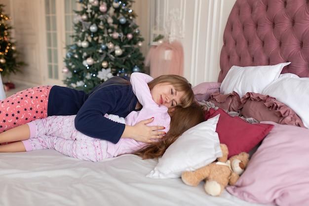 Mama kładzie dziewczynkę do łóżka w noc bożego narodzenia. świąteczna opowieść. szczęśliwe dzieciństwo.