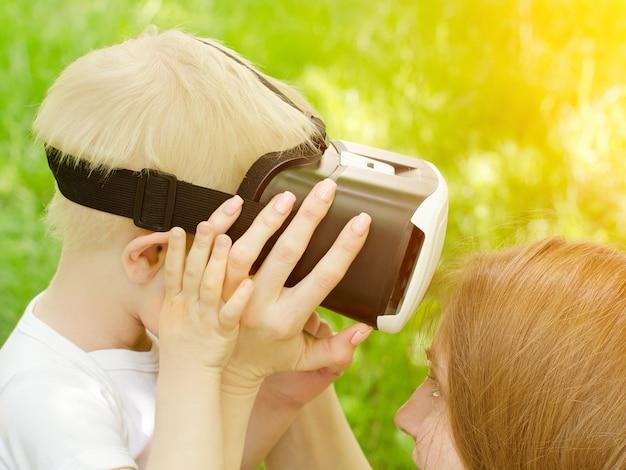 Mama koryguje okulary syna wirtualnej rzeczywistości na tle zielonej trawy