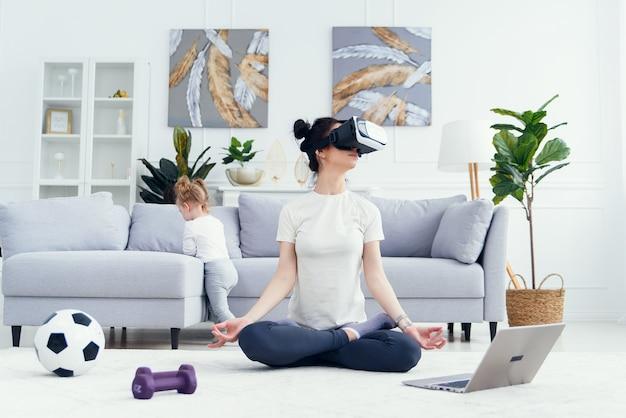 Mama medytuje w domu w pozycji lotosu jogi z córką.