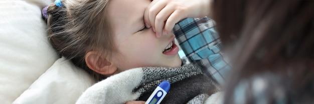 Mama mierzy temperaturę chorej dziewczynki za pomocą termometru