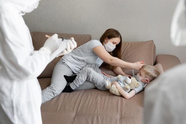 Mama mierzy temperaturę dziecka. lekarze w strojach ochronnych u chorych chorych w domu. koronawirus (covid-19