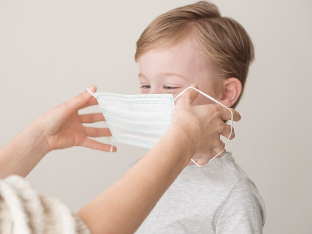 Mama nakłada maskę na chłopca