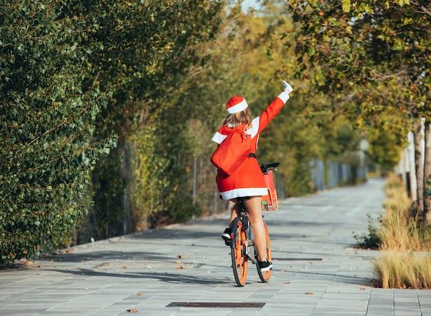 Mama noel odwrócona plecami do ulicy na rowerze. czas świąt