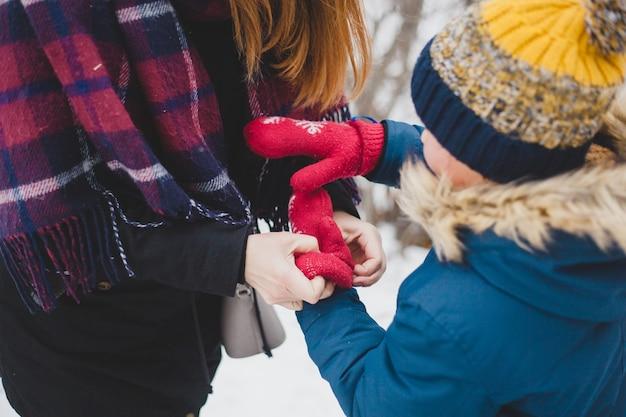 Mama nosi ciepłe rękawiczki syna spacerującego zimą, zimne, mezotyczne dłonie