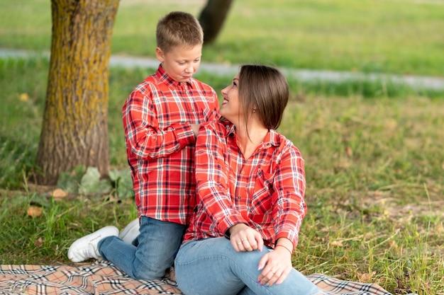 Mama, odwracając się, patrzy na syna i uśmiecha się, siedząc na narzucie. w dowolnym celu.