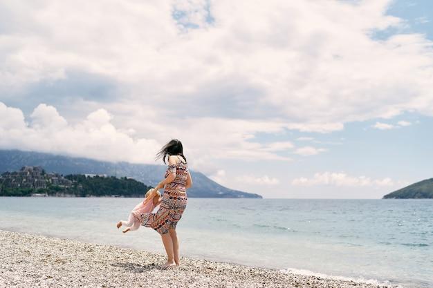 Mama okrąża małą dziewczynkę na kamienistej plaży