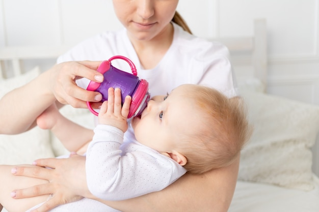 Mama pije lub butelką karmi dziecko na białym łóżku w domu, koncepcja żywności dla niemowląt.