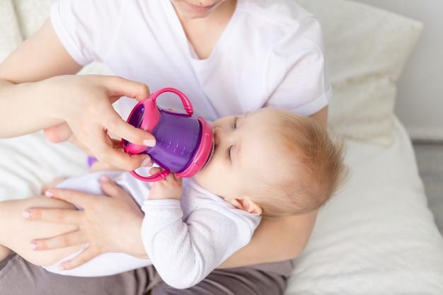 Mama pije lub karmi dziecko butelką na białym łóżku w domu, koncepcja jedzenia dla niemowląt