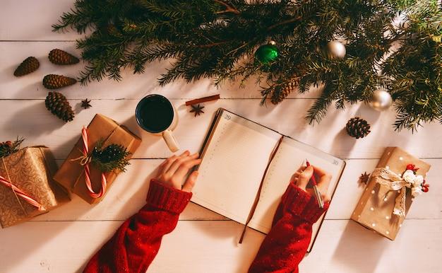 Mama pisze do notesu i listy rzeczy do zrobienia na boże narodzenie i nowy rok