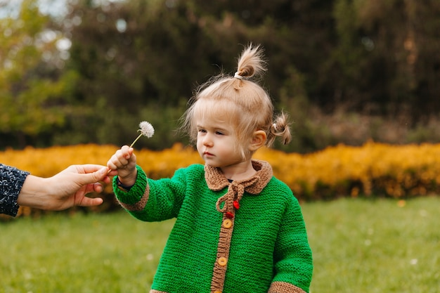 Mama podaje dziecku kwiatek. mała dziewczynka z kwiatem w parku.