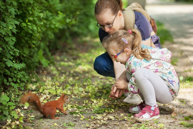 Mama pokazuje córce wiewiórkę w lesie