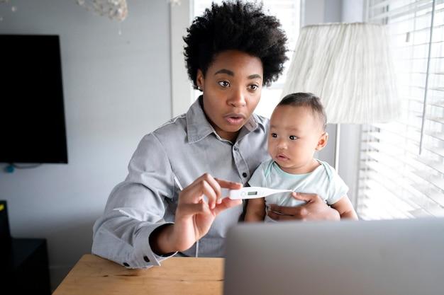 Mama pokazuje lekarzowi gorączkę dziecka przez telefon telemedyczny