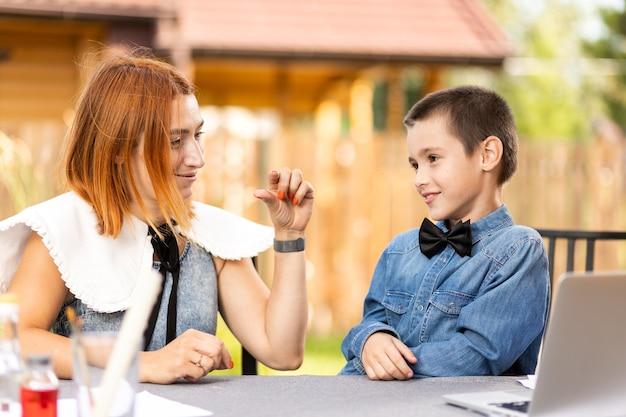 Mama pokazuje synowi rozmiar niezbędnej substancji do domowych eksperymentów chemicznych. zajęcia online dla dzieci. uczeń słucha wykładu i rozwiązuje problemy