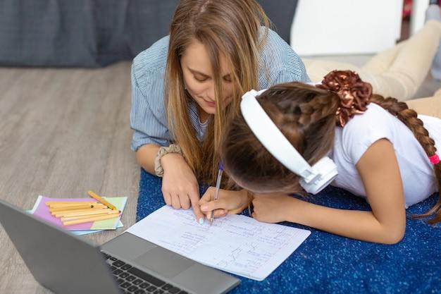 Mama pomaga córce odrabiać lekcje przed monitorem laptopa, leżąc na podłodze