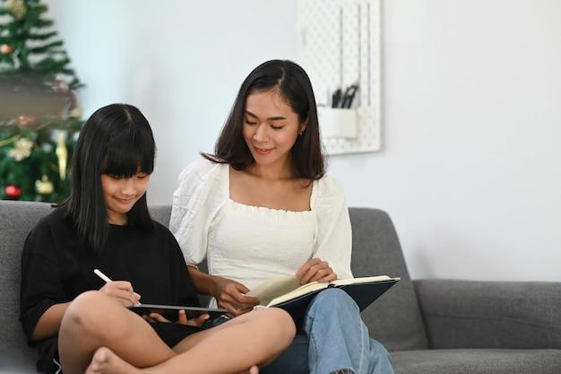 Mama pomaga córce w odrabianiu lekcji za pomocą cyfrowego tabletu, wyszukując informacje w internecie w salonie.