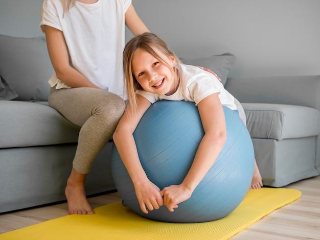 Mama pomaga dziewczynie ćwiczyć na piłce