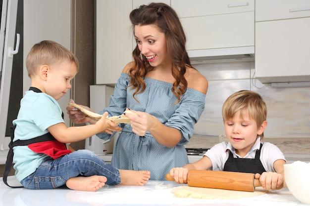 Mama pomaga młodym synom wyrabiać ciasto na kuchennym stole